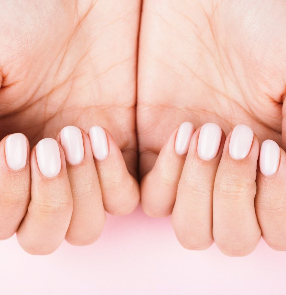 Woman's Hands with Pastel Manicure on Pink Background.